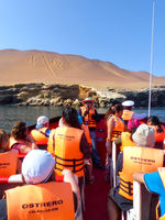 Tourist group in a boat near Candelabra of the Andes in Pisco Bay, Peru