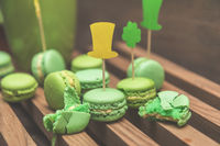 Green macaroon cookies scattered on the wooden surface with St. Patrick's Day attributes. Tinted photo. Shallow depth of field. Copy space