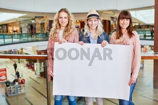 Drei Teenager halten leeres gelbes Schild