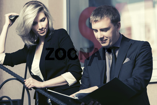 Young business couple with a folder against office window