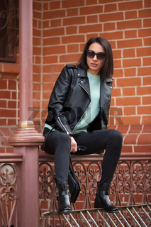 Young fashion woman in black leather jacket sitting on railing