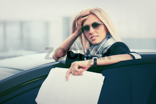 Fashion business woman with financial papers leaning on her car