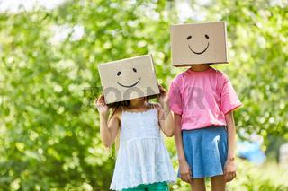 Kinder verstecken Gesichter unter Pappkartons