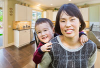 Chinese Mother and Mixed Race Child Inside Beautiful Kitchen.