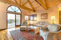 Bright, open and warm living room with vaulted ceilings and wooden beams with views in the backyard