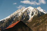 Red roof of a house on a background of a mountain with a snow-capped summit. The concept of a dwelling in the mountains. Holidays in the mountains