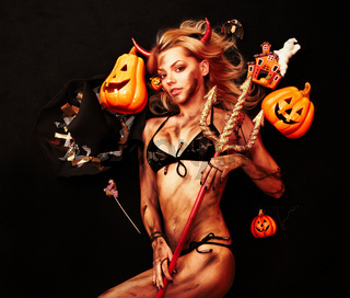 Beautiful devil with trident and Halloween accessories on black