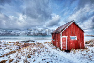 Red rorbu house shed on beach of fjord, Norway