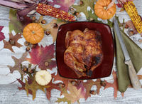 Thanksgiving turkey with autumn decorations on rustic table setting