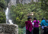 Indigenous women walk across the bridge under Devil's Cauldron waterfall (spanish: Pailon del Diablo) - Mountain river and fall in the Andes