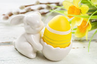 An egg cup with a yellow easter egg