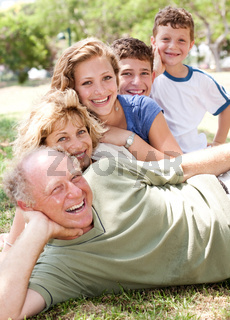 Multi-generation family relaxing in park on sunny day and smiling at camera