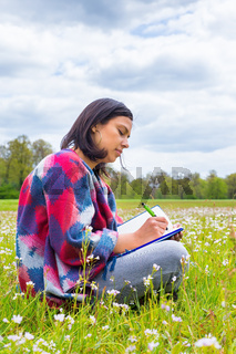 Woman writing in blooming meadow with spring flowers