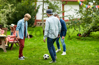 happy friends playing football at summer garden