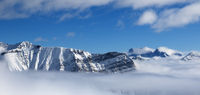 Panoramic view on snowy sunlight mountains in fog at nice sun day
