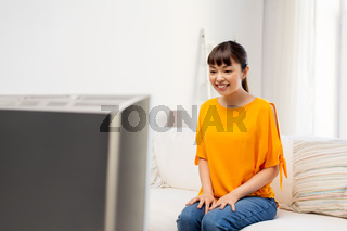 happy asian woman with watching tv at home