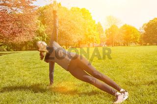 Junge Frau streckt sich bei Fitnesstraining im Park