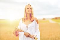happy young woman with spikelets on cereal field