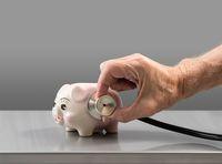 Senior male hand holding stethoscope on piggy bank