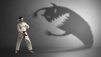 Karate man fighting with a big scary shadow