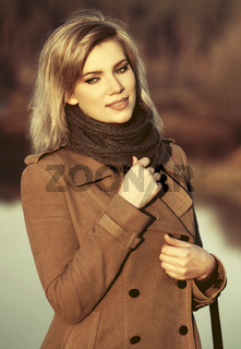 Happy young fashion blond woman walking by the lake