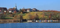 Idyllic village Seegraben in autumn. Fishing boats on lake Pfaffikersee. Colorful trees and fields.