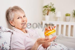 Seniorin als Patientin schluckt Tabletten