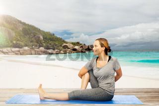 woman doing yoga in twist pose on beach