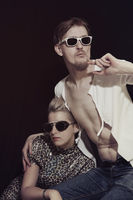 Stylish young man and woman wearing sunglasses on a black background. Fashion theme