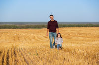 Happy father and two year old girl walking in the harvested field