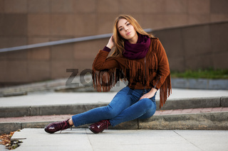 Young fashion woman in leather jacket sitting on city street