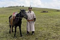 Älterer Nomade in traditioneller Kleidung mit seinem aufgezäumten Pferd in der Steppe