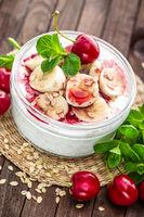 Fresh yogurt with cherry, banana and oats, healthy breakfast