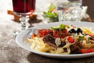 frische Pasta mit Tomaten und Oliven auf einem Teller