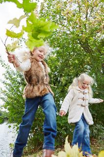 Mädchen toben und laufen auf Blättern