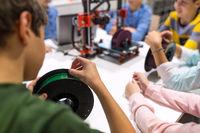 children with 3d printer at robotics school