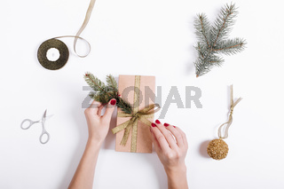 Top view of a female hands pack and decorate the box with gifts