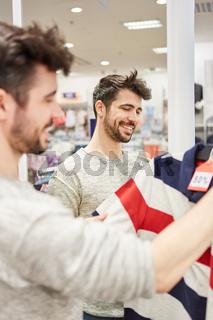 Junger Mann kauft ein Poloshirt