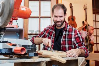Gitarrenbauer arbeitet mit dem Stechbeitel