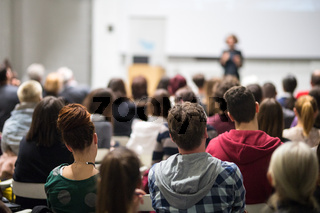 Woman giving presentation in lecture hall at university.