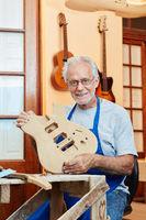 Alter Mann als stolzer Gitarrenbauer