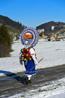 Schöner Klaus mit kunstvoll verzierter Haube bringt Neujahrsgrüsse zu einem Bauernhof