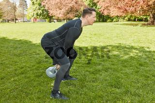 Mann trainiert mit Kettlebell im Park