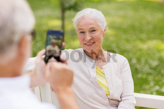 old woman photographing man by smartphone in park