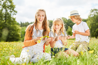 Mutter und zwei Kinder pflücken Blumen