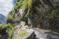 Cascades route, Banos - Puyo, Ecuador - December 8, 2017: Tourists ride bicycles along the Waterfalls Road over the precipice of the canyon