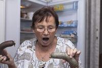 Shocked senior woman holding pork liver sausages