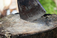 A sharp blade of an ax that sticks out in a wooden chock. rustic concept.