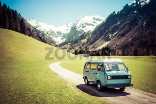 Vintage VW Bully camping car driving on mountain valley road