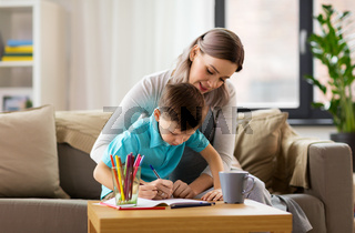 mother and son with workbook at home